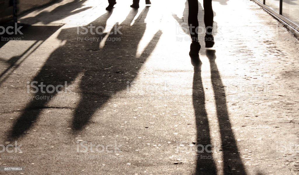 Blurry shadows and silhouettes on city sidewalk stock photo
