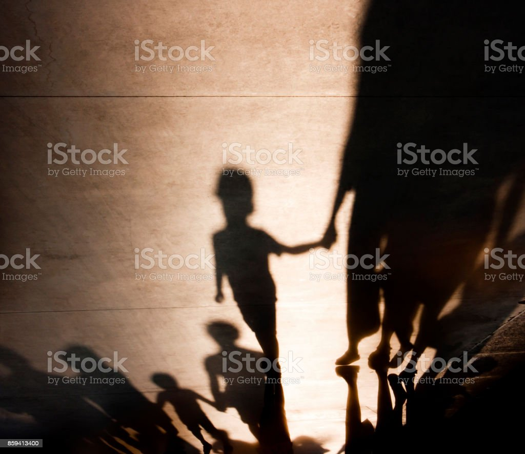 Blurry shadows of families with kids walking stock photo