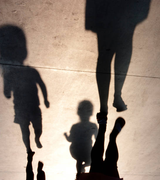 Blurry shadows of mother with two toddler kids stock photo