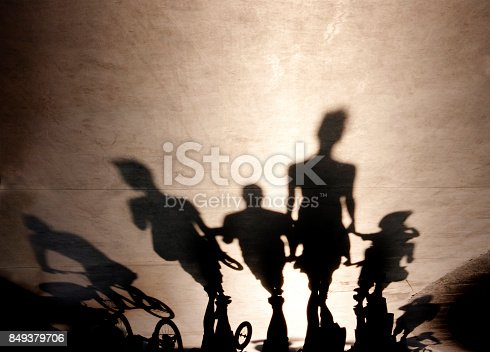 812812808 istock photo Blurry shadows of people walking on summer promenade 849379706