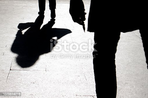 Blurry silhouette and shadow of a woman carrying a bag and a man holding sharp object following her, in the city street in the night
