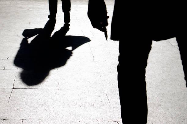 Silhueta embaçada e sombra de uma mulher que carrega um saco e um homem segurando cortantes objeto seguindo ela - foto de acervo