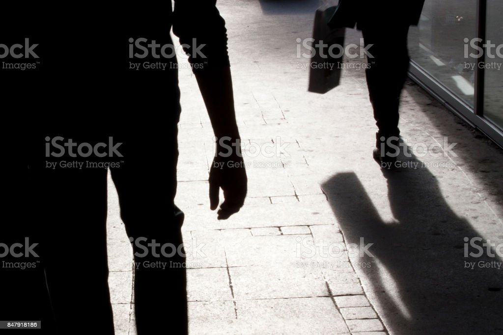 Blurry silhouette and shadows of two person walking - foto stock