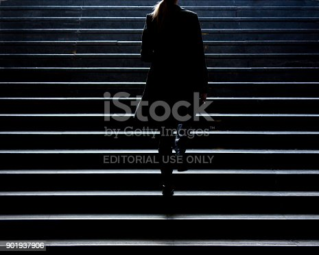 Belgrade,Serbia - December 27, 2017: Blurry silhouette of young elegant woman climbing up the stairs of underground passage in city center in winter