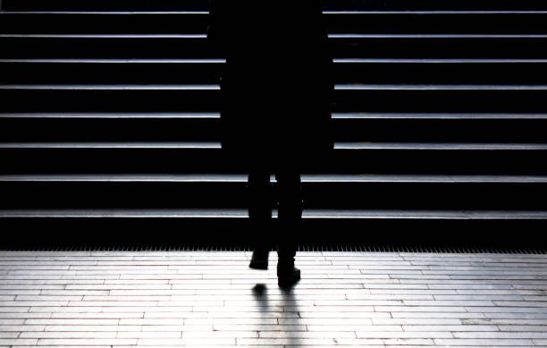 Blurry silhouette of young woman climbing up the city street stairs in winter moonlight