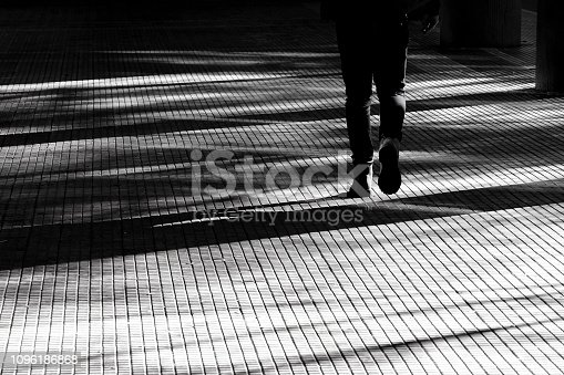 Blurry silhouette shadow of a legs of a person walking on a city arcade walkway in black and white high contrast
