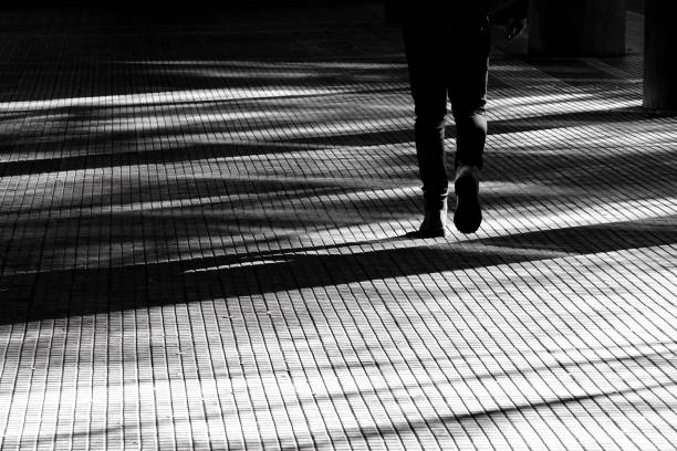 Blurry silhouette shadow of a person walking on a city arcade walkway