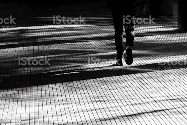 Photo of Blurry silhouette shadow of a person walking on a city arcade walkway