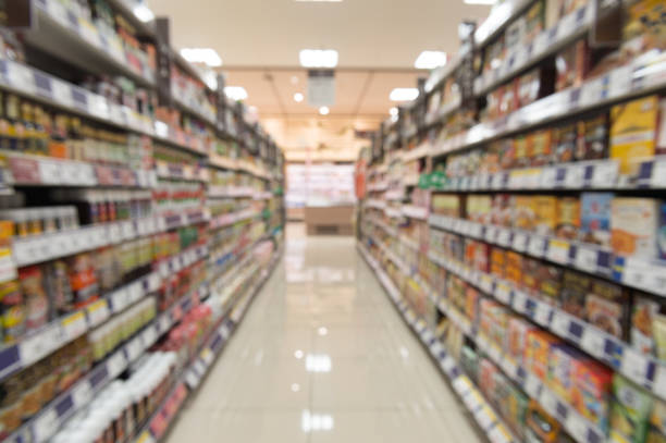 Blurry view of supermarket,Wide perspective view shelves variety of snacks, defocused blurry background bokeh light in supermarket. Business concept. Blurry view of supermarket,Wide perspective view shelves variety of snacks, defocused blurry background bokeh light in supermarket. Business concept. snack aisle stock pictures, royalty-free photos & images