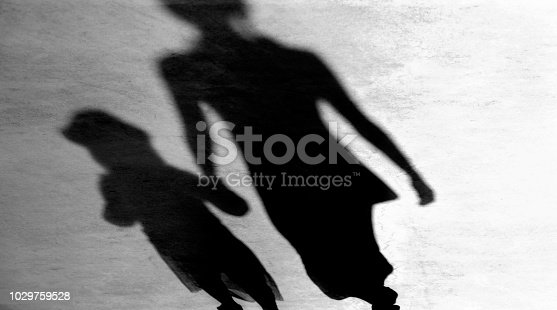 Blurry vintage shadows silhouettes of mother and daughter walking  in black and white