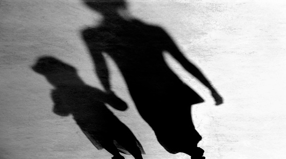 Blurry vintage shadows silhouettes of mother and daughter walking