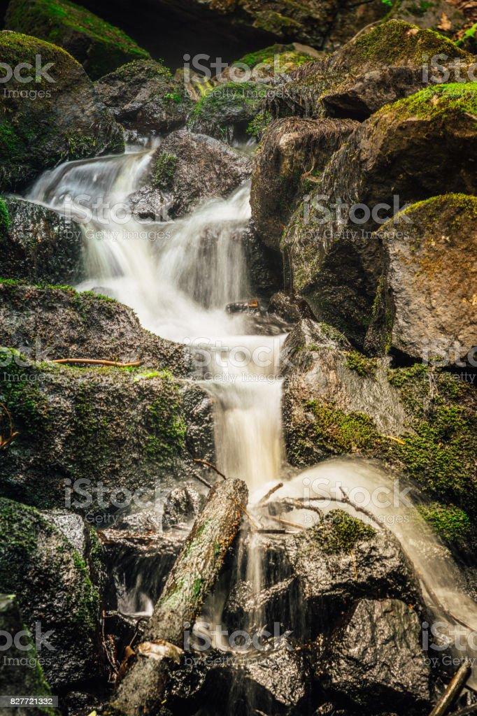 Blurry water flowing between rocks stock photo