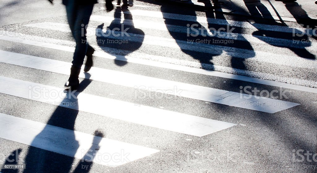 Blurry zebra crossing with pedestrians making long shadows stock photo