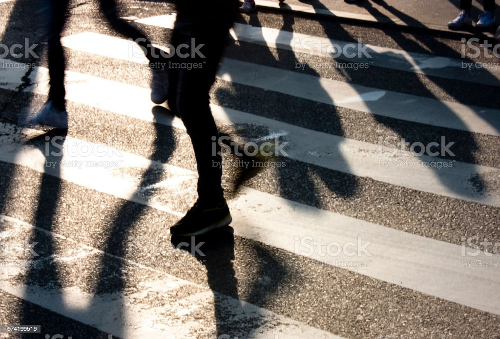 Blurry zebra crossing with  people silhouettes and  shadows stock photo