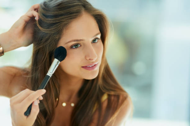 Blush brings out the best in her cheekbones Shot of an attractive young woman applying makeup to her face with a brush blusher make up stock pictures, royalty-free photos & images