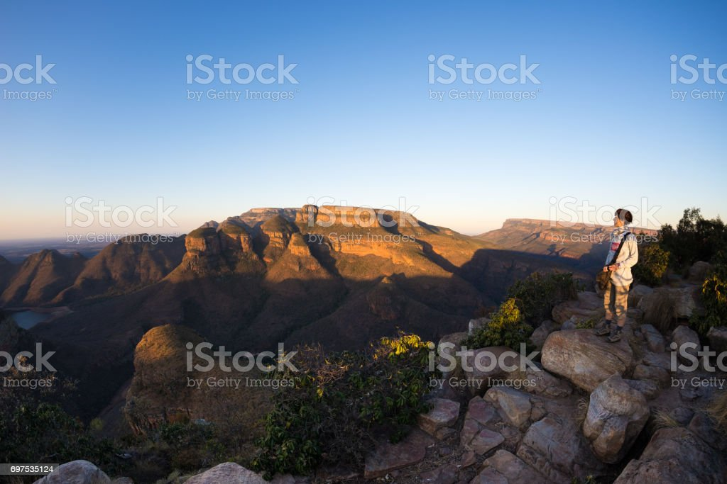 Blyde River Canyon, travel destination in South Africa. Tourist looking at panorama. Last sunlight on the mountain ridges. Fisheye distorted view from above. stock photo