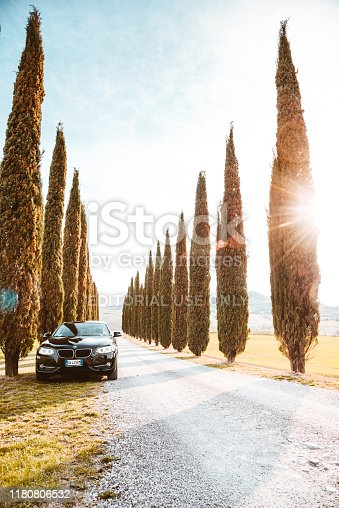 Pienza, Italy - March 12, 2017 : Brand new black coupe BMW 220d is parked at the roadside the Siena countryside along a cypress hill road. Sunny day with the sun in the background.