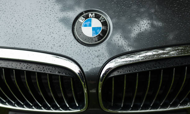 Bmw motor company badge on the front from a black car. BMW is a German automobile, motorcycle and engine manufacturing company founded in 1916 stock photo