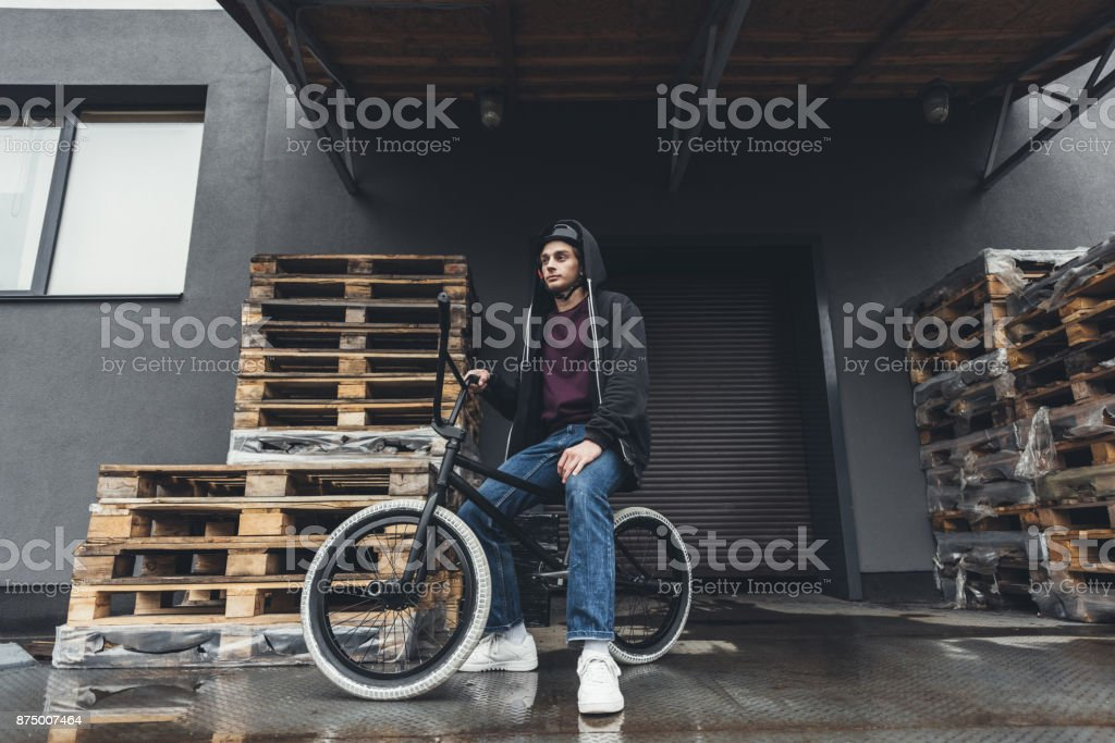 full length view of young man in helmet sitting on bmx bicycle and...