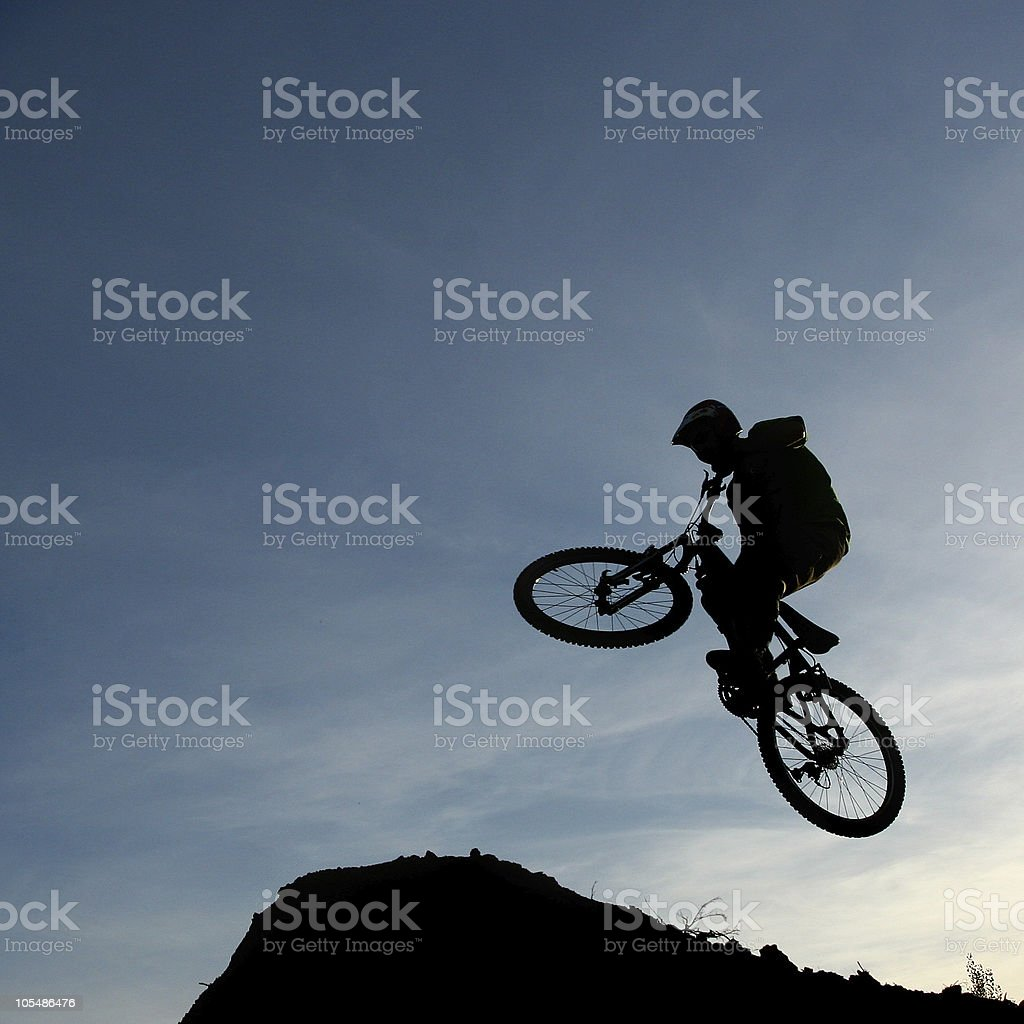 Bmx rider silhouetted jumping against early morning sky royalty-free stock photo
