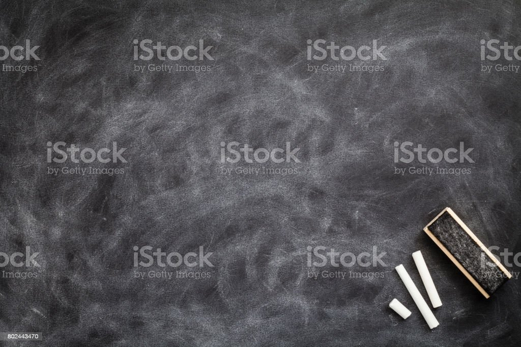 Board eraser and chalk pieces on blank blackboard with traces of erased chalk stock photo