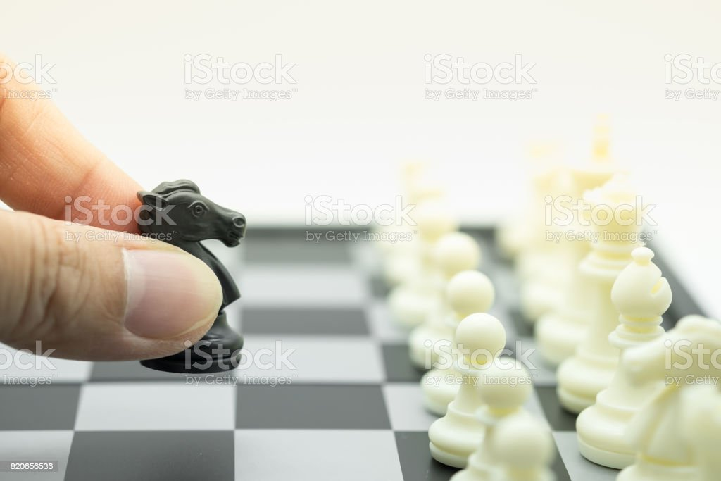 Board game, business and planning concept. Close up of man hand holding and move black chess knight piece in front of row of white pieces on chessboard. stock photo