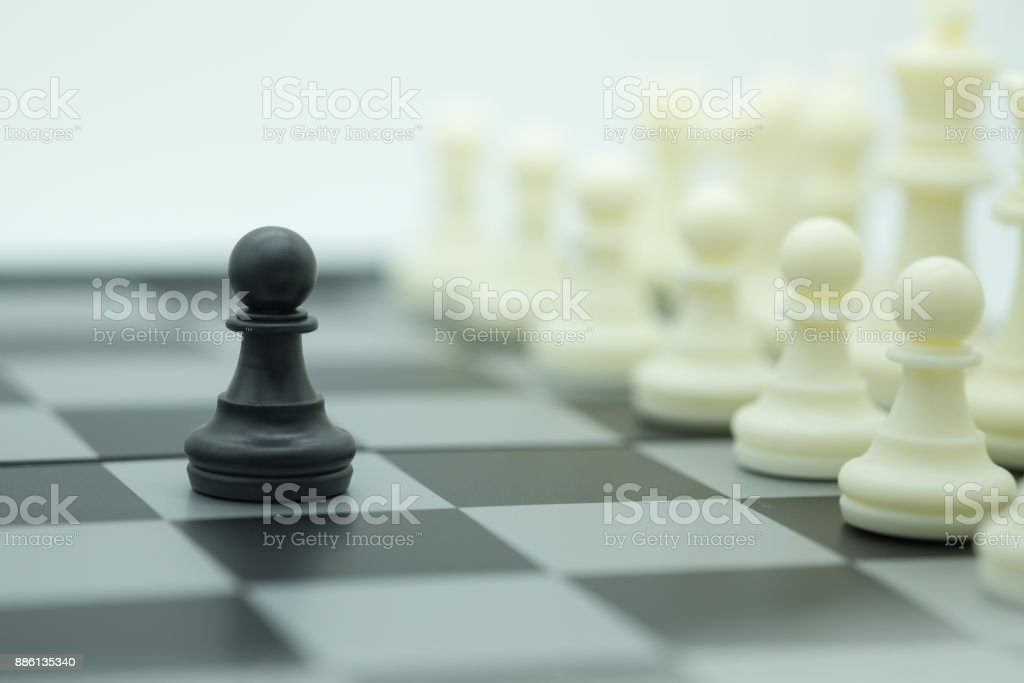 Board game, business and planning concept. Close up of pawn black chess piece in front of row of white pieces on chessboard. stock photo