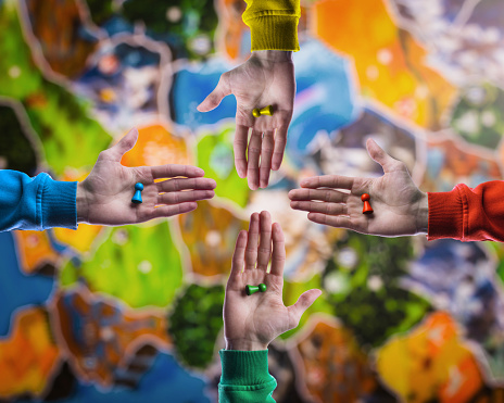 istock Board game concept- choose yours figures. People holding in hand colorful playing figures on blurred board game field background. 1067122534