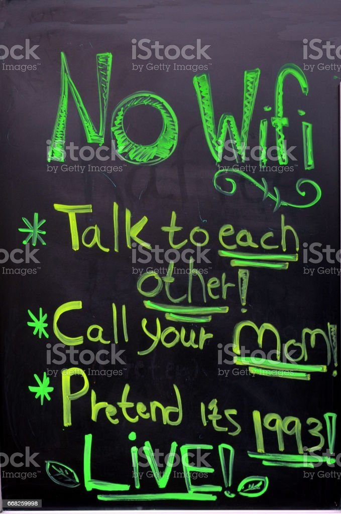 A board in front of the foodmarket  is announcing that there is No WiFi and suggests to talk to each other or call your mom or pretend it's 1993 or LIVE stock photo