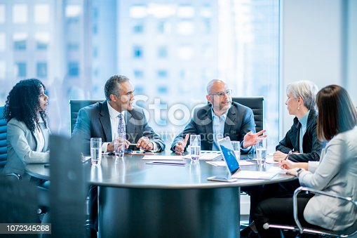 A group of five businesspeople are sitting around an office table. They are talking while having a meeting.