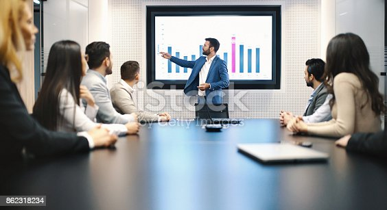 Closeup of a board room meeting at a business company, usual scene at any modern company. There are six men and three women, one of the men is speaking in front of a large screen that's showing monthly revenue of their company.