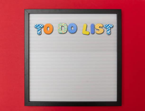 board mit schwarzem rahmen, text to do-liste in bunten buchstaben, rote wand hintergrund - unterrichtsplanung vorlagen stock-fotos und bilder