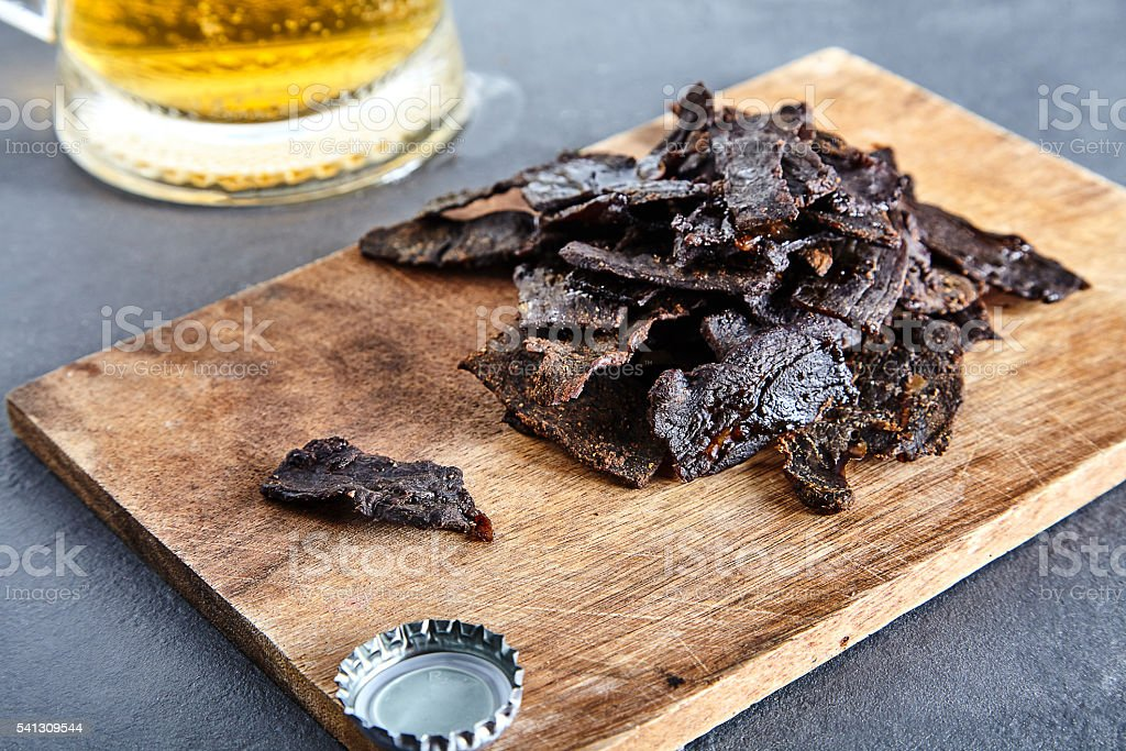 Board with homemade jerky beef and beer stock photo