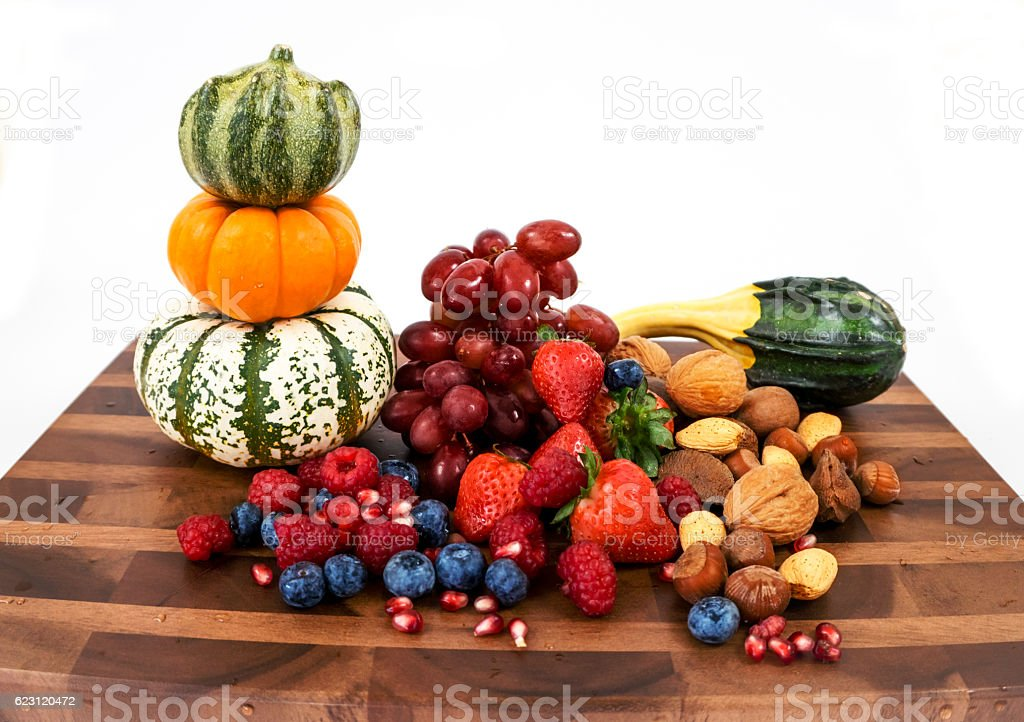 Board with seasonal fruit, pumpkins and nuts stock photo