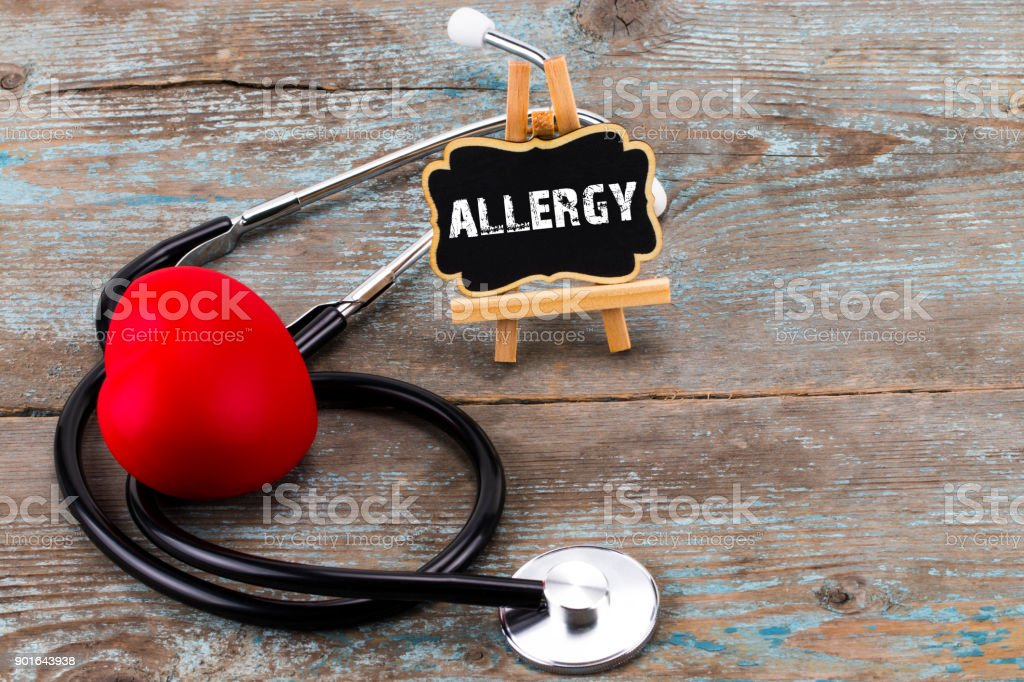 A board with the word allergy and stethoscope. The concept of medicine. A board with the word allergy and a stethoscope with a heart stock photo