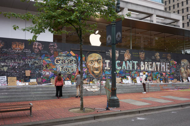 Boarded Up Apple Portland Store With Protest Murals Portland, OR, USA - Jun 12, 2020: Passers-by stop and take a look at the boarded-up Apple Store in downtown Portland's Pioneer Place, which has become unofficial canvases for peaceful protest. Artists have also joined to promote peace over violence. protest stock pictures, royalty-free photos & images