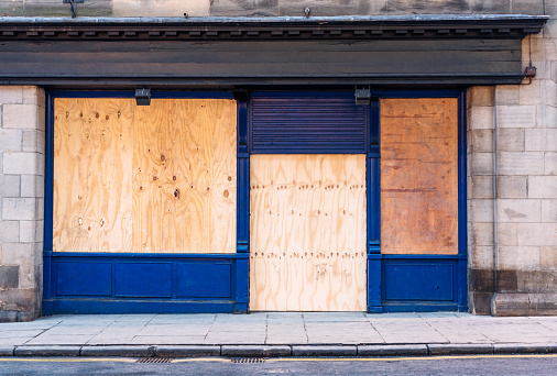 A traditional British shopfront, closed and boarded up with wooden boards.