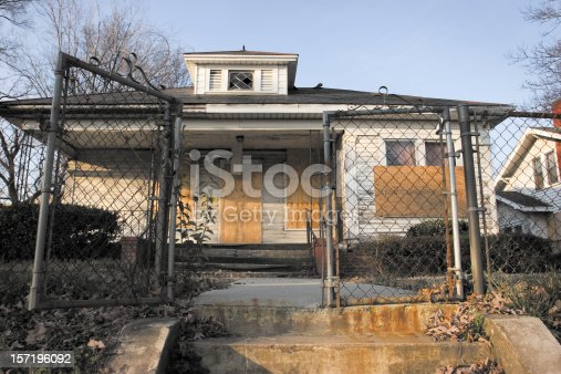 istock Boarded up small derelict house 157196092