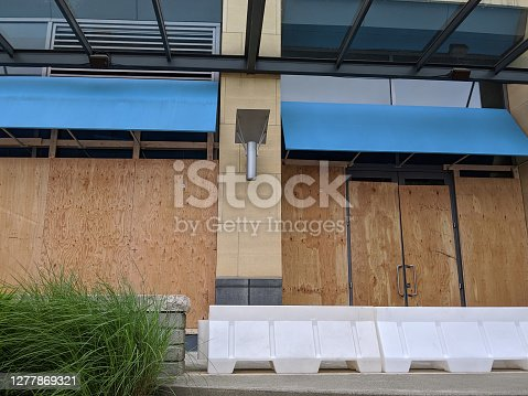 View of boarded up windows and doors in a downtown building during protests and riots amidst Covid-19