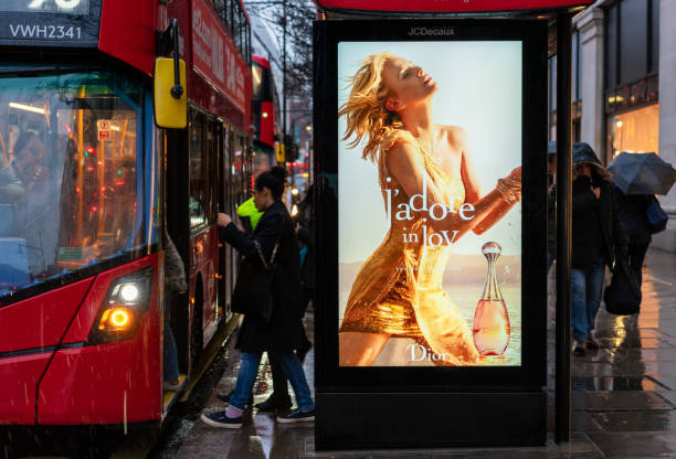 Boarding a London Bus and bus stop advertising stock photo