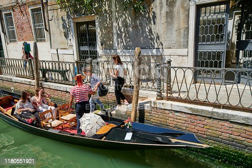 Venice, Italy - June 02, 2019: a group of female tourists boarding for a gondola tour in Fondamenta de l'Osmarin.