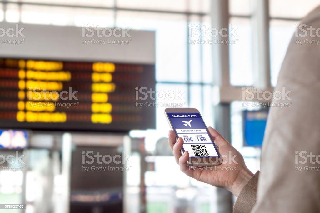 Tarjeta de embarque en smartphone. Mujer sosteniendo el teléfono en el aeropuerto con ticket móvil en la pantalla. Tecnología de viaje moderna y fácil acceso al avión. Terminal y el calendario en el fondo borroso. - foto de stock