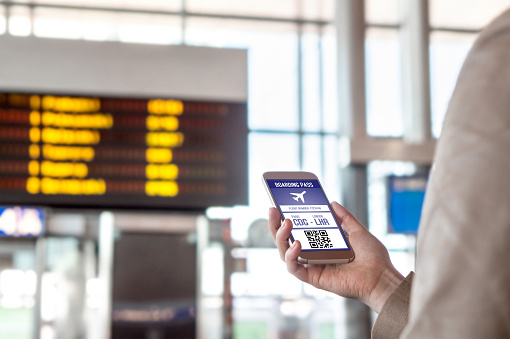 boarding pass in smartphone woman holding phone in airport
