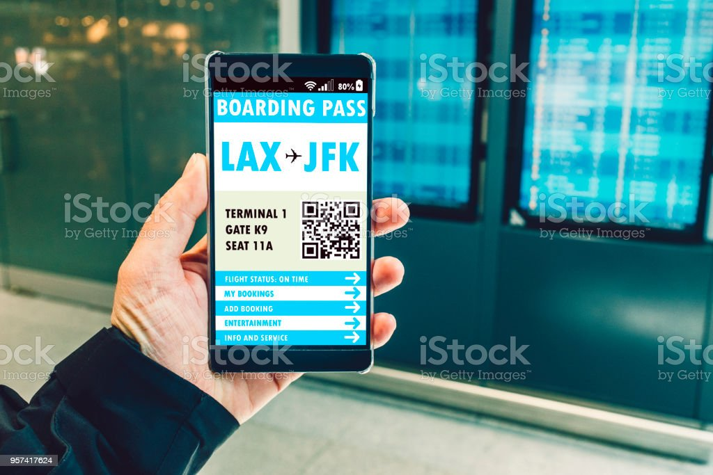 Boarding pass on mobile phone next to departure board in airport stock photo