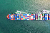 top aerial view of the large TEU containers ship arrival to the port, carriage the shipment from loading port to destination discharging port, transport and logistics services to worldwide \