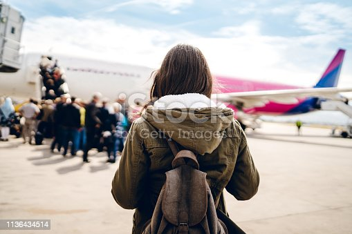 Young woman is on an airport runway, ready to board the plane