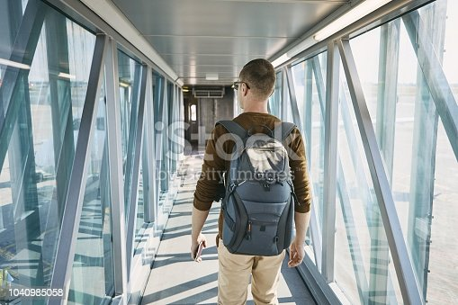 Traveling by airplane. Rear view of young man with backpack and passport in hand during boarding at airport.