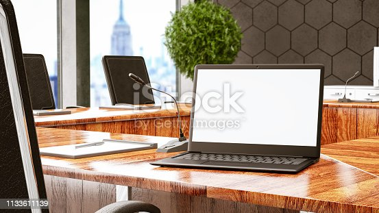 Laptop open in a boardroom with unfocused