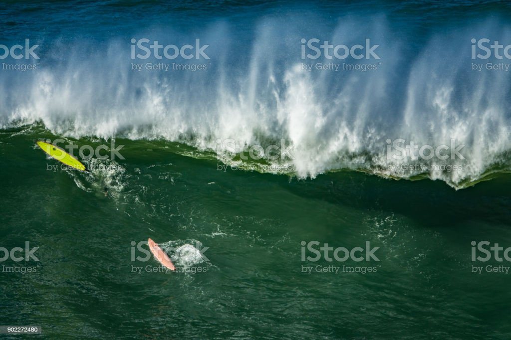 Boards of surfers duck diving in a wave stock photo