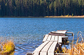 A weathered boardwalk leads to a boat dock on the rippled water of Shea Lake in the interior of BC, Canada.